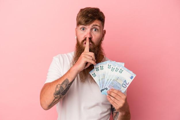 秘密を保持するか、沈黙を求めてピンクの背景に分離された紙幣を保持している長いひげを持つ若い白人生姜男。