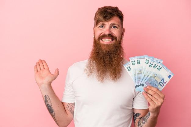 ピンクの背景に分離された紙幣を保持し、手のひらにコピースペースを示し、腰に別の手を保持している長いひげを持つ若い白人生姜男。