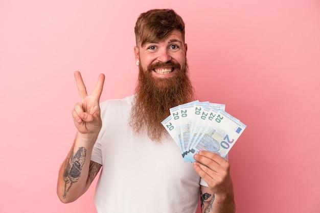 Молодой кавказский рыжий мужчина с длинной бородой держит банкноты, изолированные на розовом фоне, показывая номер два пальцами.