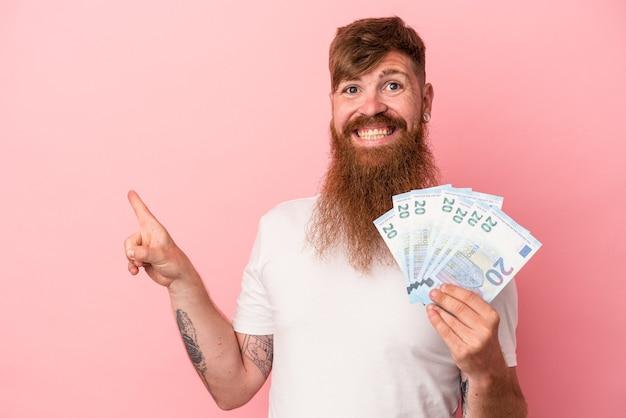 Молодой кавказский рыжий мужчина с длинной бородой держит банкноты, изолированные на розовом фоне, улыбаясь и указывая в сторону, показывая что-то на пустом месте.