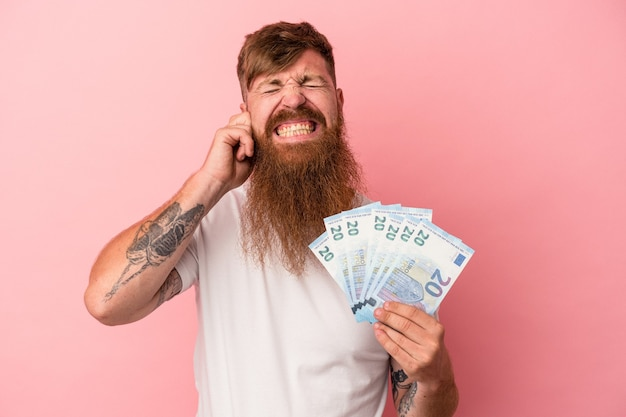 Young caucasian ginger man with long beard holding banknotes isolated on pink background covering ears with hands.