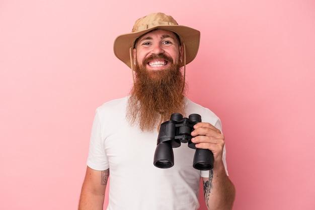 Молодой кавказский рыжий человек с длинной бородой, держащий бинокль на розовом фоне, счастливый, улыбающийся и веселый.