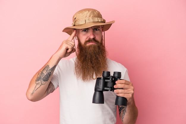 Молодой кавказский рыжий мужчина с длинной бородой держит бинокль на розовом фоне, указывая висок пальцем, думая, сосредоточившись на задаче.