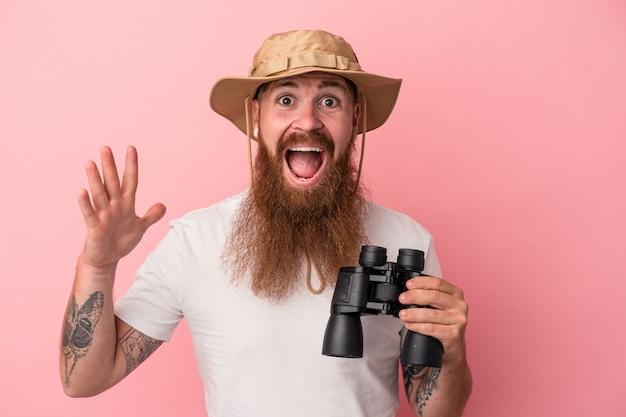 Молодой кавказский рыжий мужчина с длинной бородой держит бинокль на розовом фоне, получая приятный сюрприз, возбужденный и поднимающий руки.