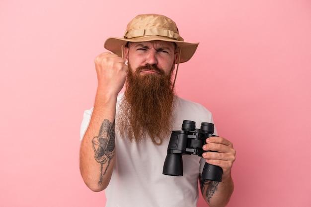 Молодой кавказский рыжий мужчина с длинной бородой держит бинокль на розовом фоне, показывая кулак на камеру, агрессивное выражение лица.