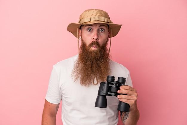 Молодой кавказский рыжий мужчина с длинной бородой, держащий бинокль на розовом фоне, пожимает плечами и смущается открытыми глазами.