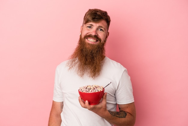 Young caucasian ginger man with long beard holding a bowl of cereales isolated on pink background happy, smiling and cheerful.