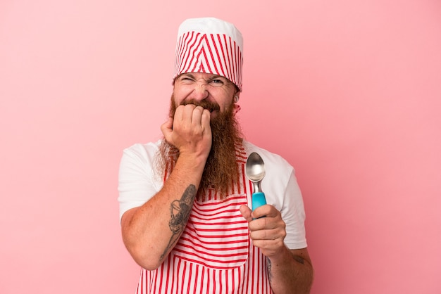 Young caucasian ginger man with long beard holding a scoop isolated on pink background biting fingernails, nervous and very anxious.