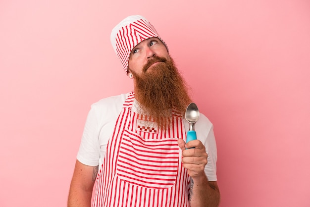 Young caucasian ginger man with long beard holding a scoop isolated on pink background dreaming of achieving goals and purposes