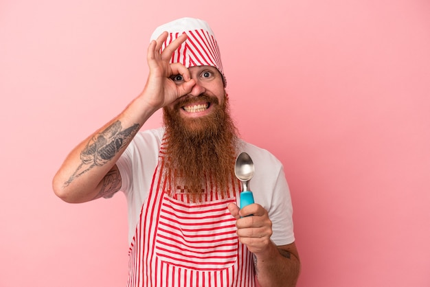 Young caucasian ginger man with long beard holding a scoop isolated on pink background excited keeping ok gesture on eye.