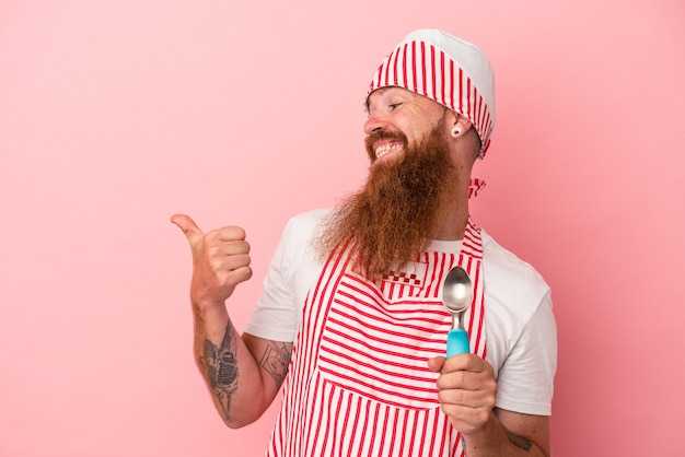 Young caucasian ginger man with long beard holding a scoop isolated on pink background points with thumb finger away, laughing and carefree.