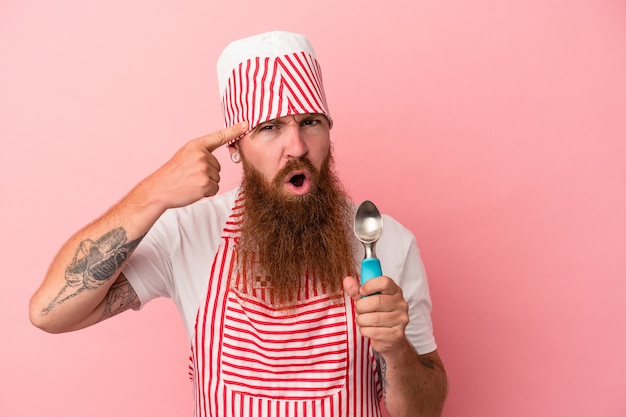 Young caucasian ginger man with long beard holding a scoop isolated on pink background showing a disappointment gesture with forefinger.