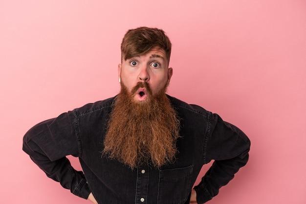 彼女が見た何かのためにショックを受けているピンクの背景に分離された長いひげを持つ若い白人の生姜男。