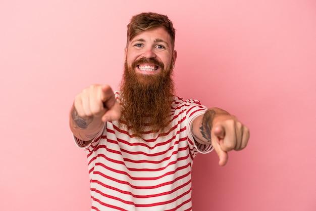 ピンクの背景に分離された長いあごひげを持つ若い白人生姜男は、正面を指している陽気な笑顔。