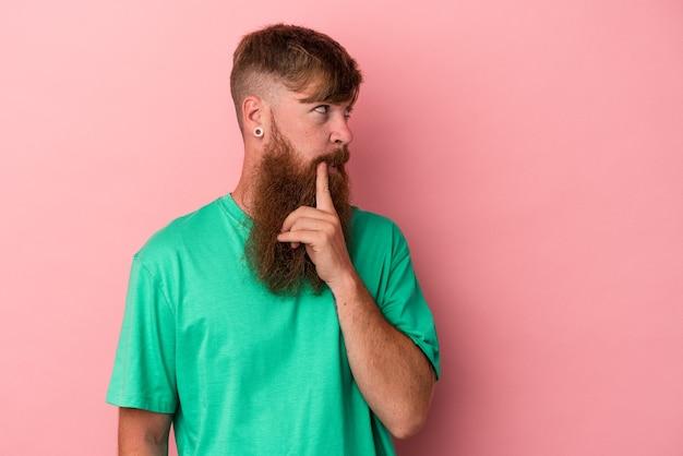 ピンクの背景に孤立した長いひげを持つ若い白人の生姜男は、ビジネスの方法を考え、戦略を計画し、考えています。