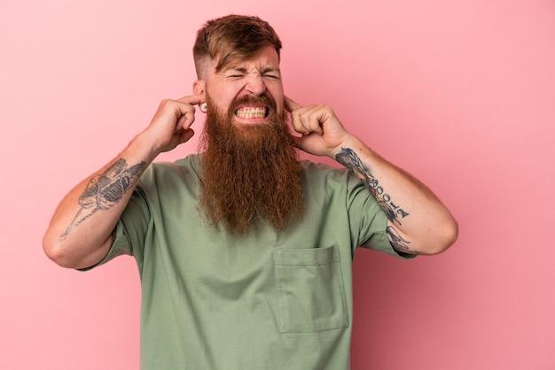 指で耳を覆っているピンクの背景に分離された長いあごひげを持つ若い白人の生姜男は、大声で周囲によってストレスと絶望的です。