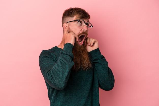ピンクの背景に指で耳を覆っている長いあごひげを生やした若い白人の生姜男は、大声で周囲にストレスと絶望的です。