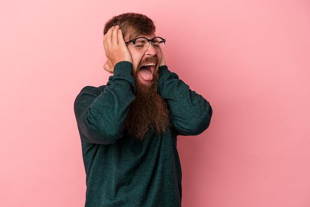 Молодой кавказский рыжий мужчина с длинной бородой изолирован на розовом фоне, закрывая уши руками, пытаясь не слышать слишком громкий звук.