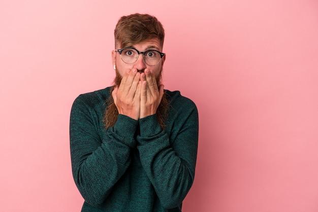 Молодой кавказский рыжий мужчина с длинной бородой изолирован на розовом фоне, покрывая рот руками, выглядящими обеспокоенными.