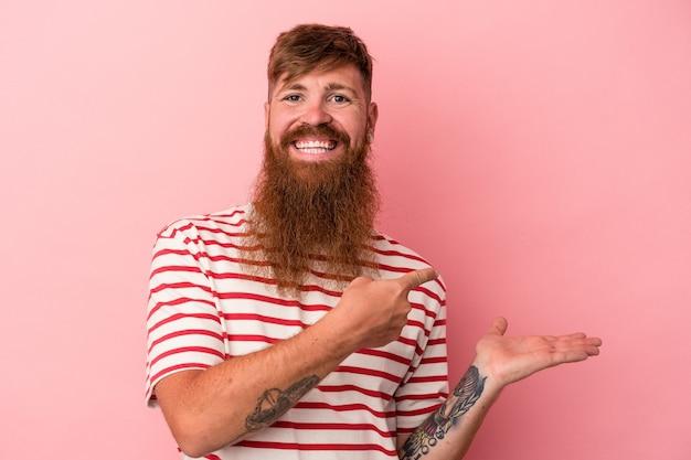 ピンクの背景に分離された長いひげを持つ若い白人の生姜男は、手のひらにコピースペースを保持して興奮しました。
