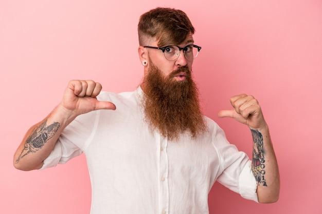 ピンクの背景に分離された長いあごひげを持つ若い白人の生姜の男は、誇りと自信を持っていると感じています。