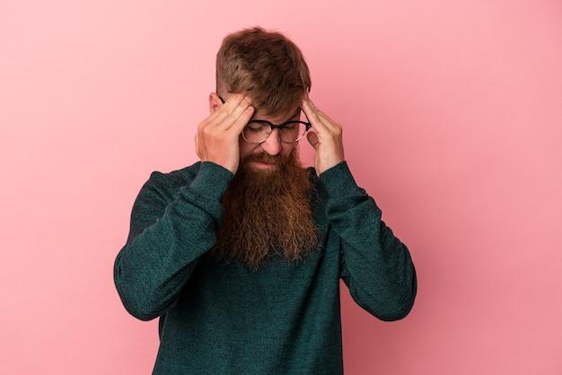 顔の正面に触れて、頭痛を持っているピンクの背景に分離された長いひげを持つ若い白人生姜男。