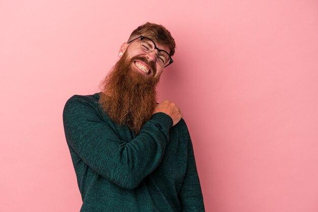 Молодой кавказский рыжий мужчина с длинной бородой, изолированной на розовом фоне с болью в плече.