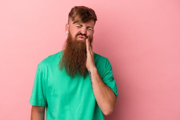 強い歯の痛み、臼歯の痛みを持っているピンクの背景に分離された長いひげを持つ若い白人の生姜男。