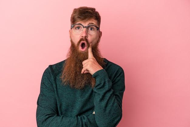 ピンクの背景に分離された長いひげを持つ若い白人の生姜男は、いくつかの素晴らしいアイデア、創造性の概念を持っています。