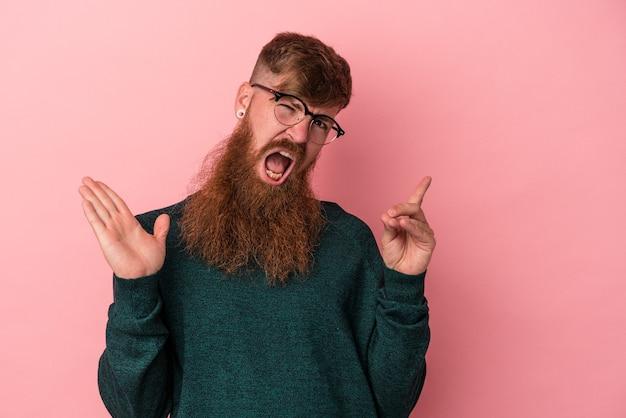 Молодой кавказский рыжий человек с длинной бородой, изолированной на розовом фоне, держа и показывая продукт под рукой.