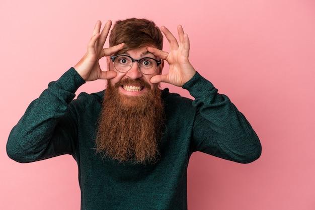 Молодой кавказский рыжий мужчина с длинной бородой, изолированной на розовом фоне, держа глаза открытыми, чтобы найти возможность успеха.