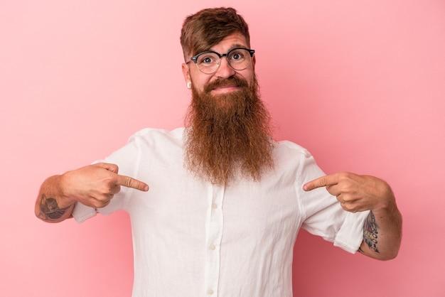 誇りと自信を持って、シャツのコピースペースを手で指しているピンクの背景の人に分離された長いひげを持つ若い白人生姜男