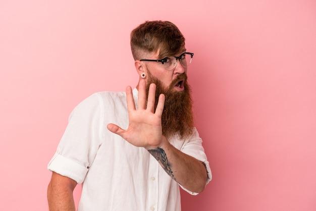 嫌悪感のジェスチャーを示す誰かを拒否するピンクの背景に分離された長いひげを持つ若い白人生姜男。