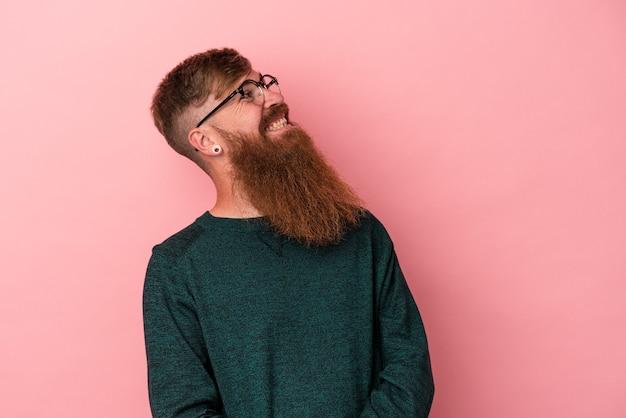 Молодой кавказский рыжий мужчина с длинной бородой, изолированной на розовом фоне, расслабленный и счастливый смех, вытянув шею, показывая зубы.