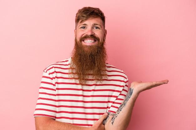 ピンクの背景に分離された長いひげを持つ若い白人の生姜男は、手のひらにコピースペースを示し、腰に別の手を保持しています。