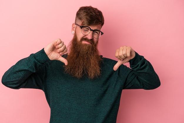 親指を下に、失望の概念を示すピンクの背景に分離された長いひげを持つ若い白人生姜男。
