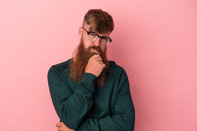ピンクの背景に孤立した長いひげを持つ若い白人の生姜男は、考えて見上げ、反射し、熟考し、ファンタジーを持っています。