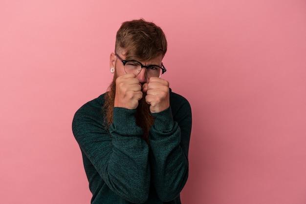 ピンクの背景に孤立した長いひげを持つ若い白人生姜男は、パンチ、怒り、議論のために戦う、ボクシングを投げます。