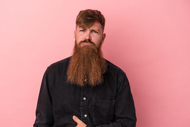 ピンクの背景に分離された長いひげを持つ若い白人生姜男はおなかに触れ、優しく微笑んで、食べて満足の概念。