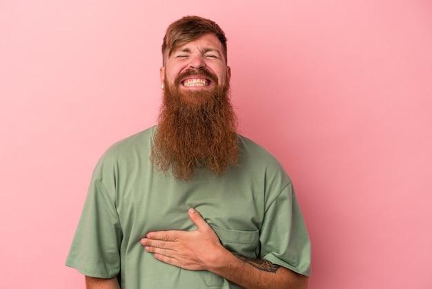 분홍색 배경에 격리된 긴 수염을 가진 젊은 백인 생강 남자는 배를 만지고, 부드럽게 웃고, 먹고, 만족스러운 개념을 갖습니다.