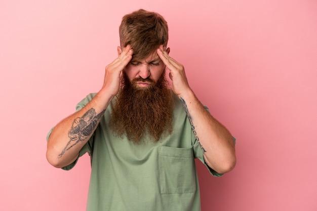 寺院に触れて頭痛を持っているピンクの背景に分離された長いひげを持つ若い白人生姜男。