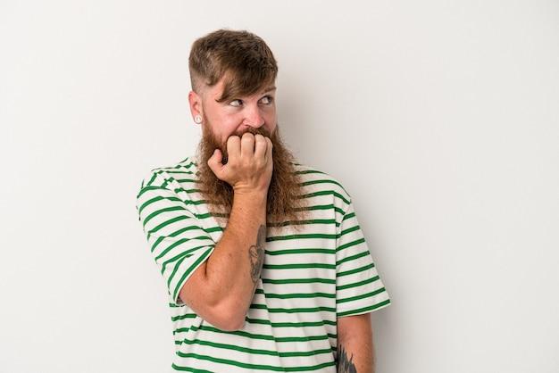 指の爪を噛んで、神経質で非常に心配している白い背景で隔離の長いひげを持つ若い白人の生姜男。