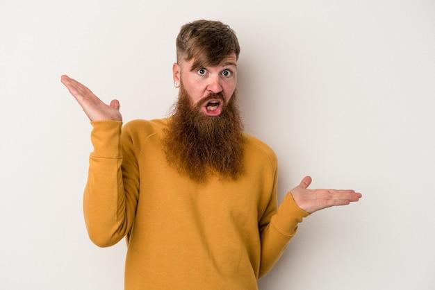 白い背景で隔離された長いひげを持つ若い白人の生姜男は、コピースペースを保持するために混乱し、疑わしい肩をすくめる肩をします。