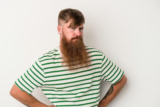 白い背景で隔離の長いひげを持つ若い白人の生姜男は混乱し、疑わしく、不安を感じます。