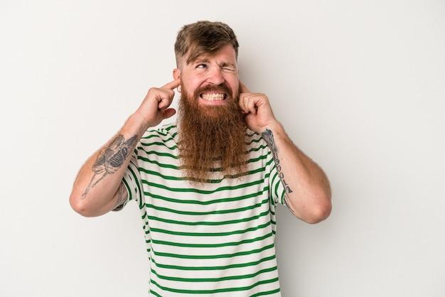 指で耳を覆っている白い背景に分離された長いひげを持つ若い白人の生姜男は、大声で周囲によってストレスと絶望的です。
