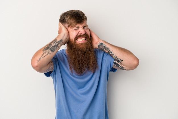 手で耳を覆う白い背景で隔離の長いひげを持つ若い白人生姜男。