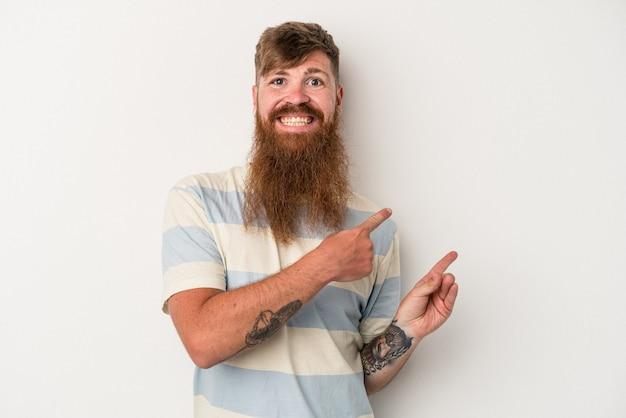 白い背景に分離された長いあごひげを持つ若い白人の生姜男は、人差し指を離れて指して興奮しました。
