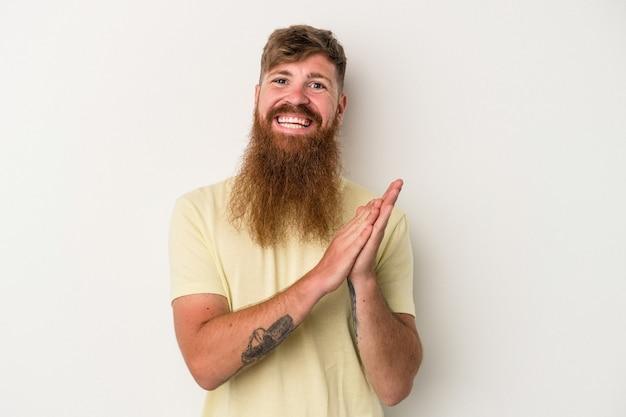 エネルギッシュで快適な感じ、自信を持って手をこすりながら、白い背景で隔離の長いひげを持つ若い白人生姜男。