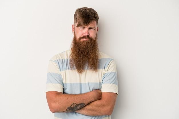 不快な顔をしかめている白い背景に長いあごひげを生やした若い白人の生姜男は、腕を組んでいます。