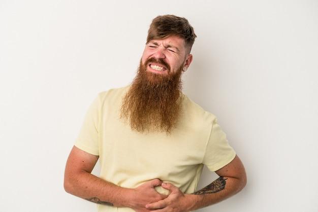 肝臓の痛み、胃の痛みを持っている白い背景で隔離の長いひげを持つ若い白人生姜男。